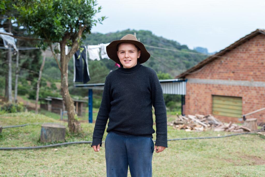 Menino branco de chapéu de palha, camiseta preta e calça jeans em frente a um galpão de tijolos à vista, na zona rural de Antonio Prado